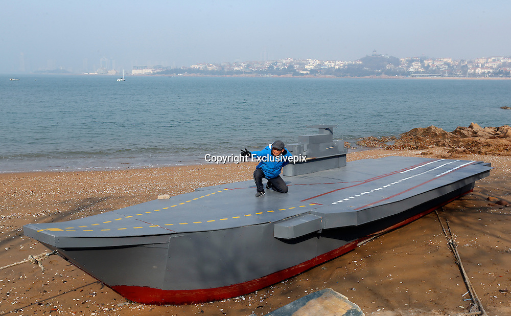 QINGDAO, CHINA - MARCH 04: (CHINA OUT) <br /> <br /> Man-Made Aircraft Carrier <br /> <br /> 80-year-old Wen Yuzhu shows his mad-made aircraft carrier model on March 4, 2014 in Qingdao, Shandong Province of China. The 12 meter long, 2 meter wide model is painted with grey and yellow runways. It took Wen over a month to finish the model. The idea comes out from a word of his grandson who studies overseas. &quot;You've made many sailing boats in your life, why not making an aircraft carrier?&quot; Then When started to make the aircraft carrier model from painting a blueprint.<br /> &copy;Exclusivepix