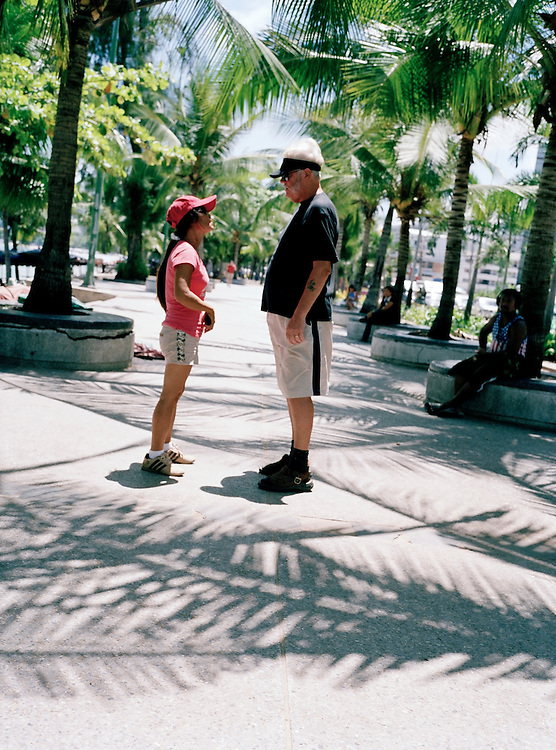 A western man and Thai woman converse on Pattaya's beach promenade.