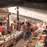 Vendors at the morning market in Phonsavan in northeast Laos sell a wide range of freshly cooked food and local cuisine delicacies, including grilled sparrow, pork, chicken, insects, and dog. The people of the region are predominantly of Hmong ethnicity.