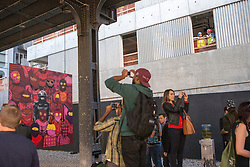 "Banksy graffiti art in New York City. Friday, 18 October 2013. Construction workers watch as people take pictures of graffiti artist Banksy's new piece for the 18th of October which is located on 24th St. between 10th and 11th Aves. The pieces are suspended from the bottom of the High-line, an elevated park in Manhattan. Banksy is doing an artist in residence, titled ""Better Out Than In"" on the streets of New York for the month of October. Picture by Michael Graae / i-Images"