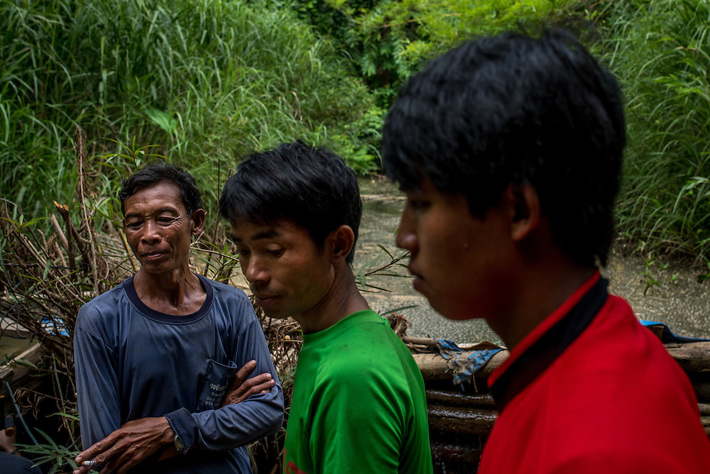 Men gather near a small water turbine in the village of Khoc Kham.