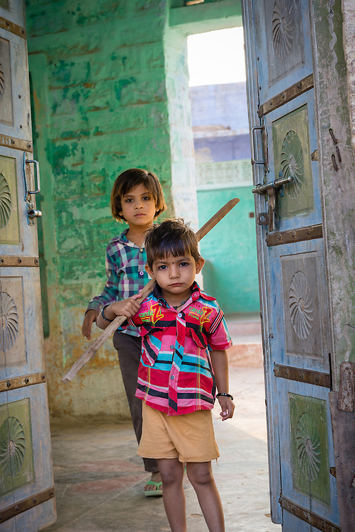 Children standing in doorway of home in village of Chandelao