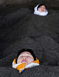 Two women in hot sand bath at Ibusuki Kyushu Japan