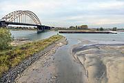 Nederland, Nijmegen, 5-11-2015 De waterstand in de rivier de Waal is laag. Woonboten in een rivierarm in de buurt van de stad liggen op het droge of vallen bijna droog. Binnevaartschepen nemen minder lading, vracht in en moeten goed in de vaargeul blijven. Hierdoor is het drukker op de rivier. Gestolenn fietsen komen ook tevoorschijn.Foto: Flip Franssen/Hollandse Hoogte