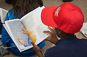 """Students read """"The Wall"""" with marines during the reveal of the 32 finalists in the Houston ISD NCAA Read to the Final Four, November 11, 2015."""