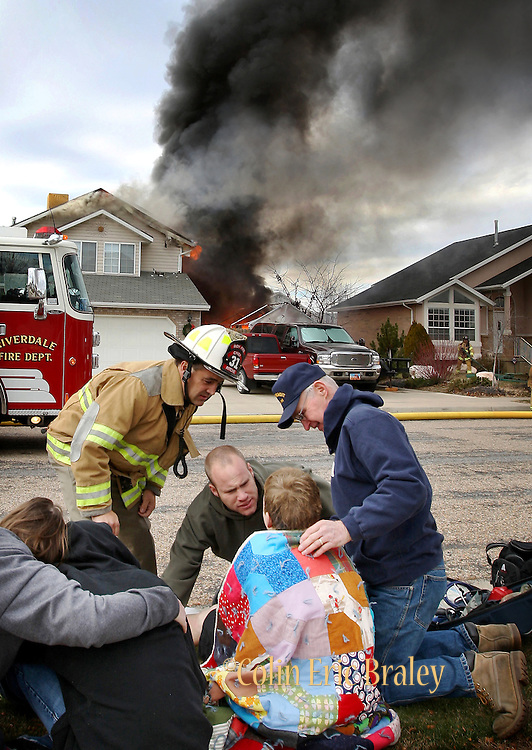 An unidentified male teenager (center) receives medical attention after he was burned in a fire at 4133 South, 2225 West in Roy, November 29, 2007. The teen was airlifted to University of Utah Hospital's Burn Center. Photo by Colin Braley