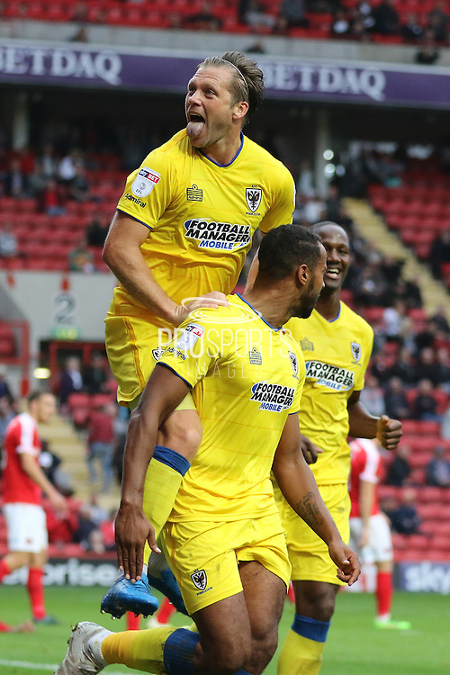 AFC Wimbledon midfielder Dannie Bulman (4) celebrates with AFC Wimbledon striker Tyrone Barnett (23) during the EFL Sky Bet League 1 match between Charlton Athletic and AFC Wimbledon at The Valley, London, England on 17 September 2016. Photo by Stuart Butcher.