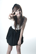 Smiling teen gestures the Peace sign with her fingers