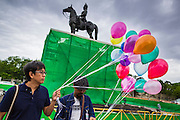 "24 JUNE 2014 - BANGKOK, THAILAND: Members of the ""Monsoon Poets Society"" carry helium balloons past the statue of King Rama V in front of the Anantasamakom Throne Hall Tuesday to pay homage to the People's Party, a Siamese (Thai) group of military and civil officers (which became a political party) that staged a bloodless coup against King Prajadhipok (Rama VII) and changed Thailand (then Siam) from an absolute monarchy to a constitutional monarchy on 24 June 1932. Since the coup against the civilian government on 22 May, the ruling junta has not allowed political gatherings. Although police read the poems, they did not arrest any of the poets or make any effort to break up the gathering.     PHOTO BY JACK KURTZ"