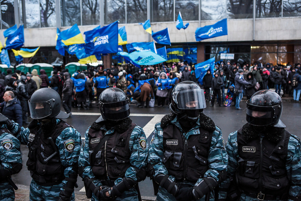 KIEV, UKRAINE - DECEMBER 8: Berkut police officers hold back anti-government protesters near a street that leads to the Ukrainian parliament building, the site of a rally held by the ruling Party of Regions in support of the government and Ukrainian president Viktor Yanukovych, on December 8, 2013 in Kiev, Ukraine. Thousands of people have been protesting against the government since a decision by President Yanukovych to suspend a trade and partnership agreement with the European Union in favor of incentives from Russia. (Photo by Brendan Hoffman/Getty Images) *** Local Caption ***