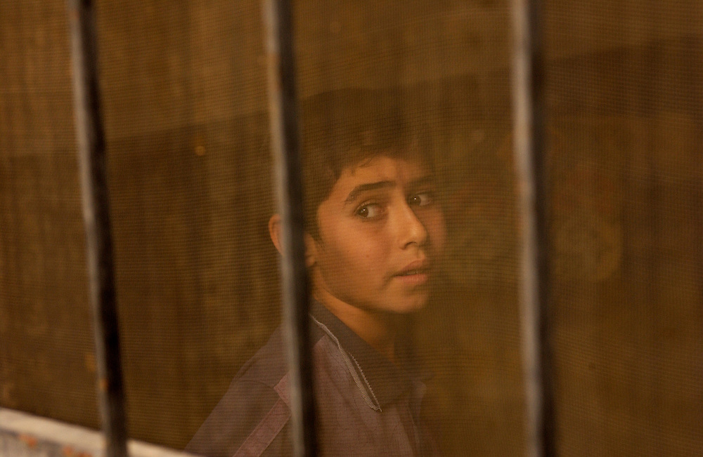 A Iraqi boys looks on with fear as soldiers enter his house.