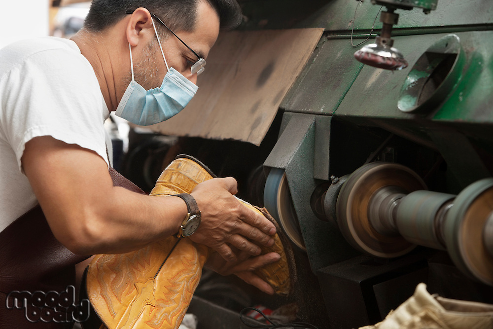 Side view of mature shoemaker rubbing sole in machinery