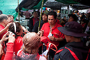 One of the leaders of Red Shirts, Arisman Pongruangrong (a former singer who turned to politics) , is appearing to his supporters in the barricaded camp of Ratchaprasong, Bangkok, sunday 18 april, after he had escaped from police operation a week before.  Around him bodyguards are looking at rooftops around. He didn't surrender with others leaders when the army took the camp the May 19 2010 and is still on the run to avoid a trial. (updated: Apr. 20 2011. (see also Natthawut Saikua)