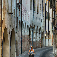 TREVISO, ITALY - AUGUST 24:  A woman rides her bike along a street on a traditional part of Treviso on August 24, 2013 in Treviso, Italy. Treviso claims that Tiramisu was invented in the 1960s by Alba Campeol, the owner of the Restaurant called ÒAlle BeccherieÓ, who supposedly wanted to create a dessert that would give her an energy boost after the birth of her son.  (Photo by Marco Secchi/Getty Images)