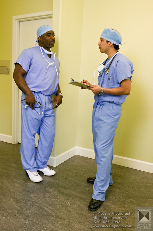 Two male doctors in OR scrubs having a discussion in the hallway of a medical office, Tucson, Arizona..Media Usage:.Subject photograph(s) are copyrighted Edward McCain. All rights are reserved except those specifically granted by McCain Photography in writing...McCain Photography.211 S 4th Avenue.Tucson, AZ 85701-2103.(520) 623-1998.mobile: (520) 990-0999.fax: (520) 623-1190.http://www.mccainphoto.com.edward@mccainphoto.com
