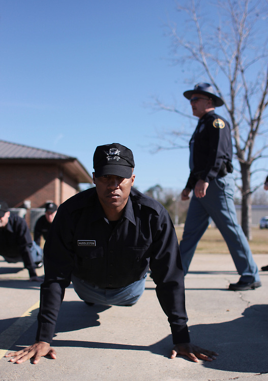 Hattiesburg Police officer Bryan Morse walks past new recruits for the Hattiesburg Police Department as  they do push-ups on Wednesday morning during the second day of a training at the Hattiesburg Police Academy. Bryant Hawkins/The Hattiesburg American
