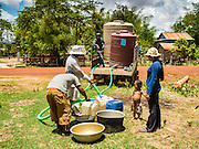 03 JUNE 2016 - SIEM REAP, CAMBODIA:  Volunteers from Water on Wheels fill villagers water jugs at a water distribution point in Sot Nikum, a village northeast of Siem Reap. Wells in the village have been dry for more than three months because of the drought that is gripping most of Southeast Asia. They were waiting for water brought in by truck from Siem Reap by Water on Wheels, a NGO in Siem Reap. Cambodia is in the second year of  a record shattering drought, brought on by climate change and the El Niño weather pattern. There is no water to irrigate the farm fields and many of the wells in the area have run dry. People are being forced to buy water or get water from NGOs to meet their domestic needs.    PHOTO BY JACK KURTZ