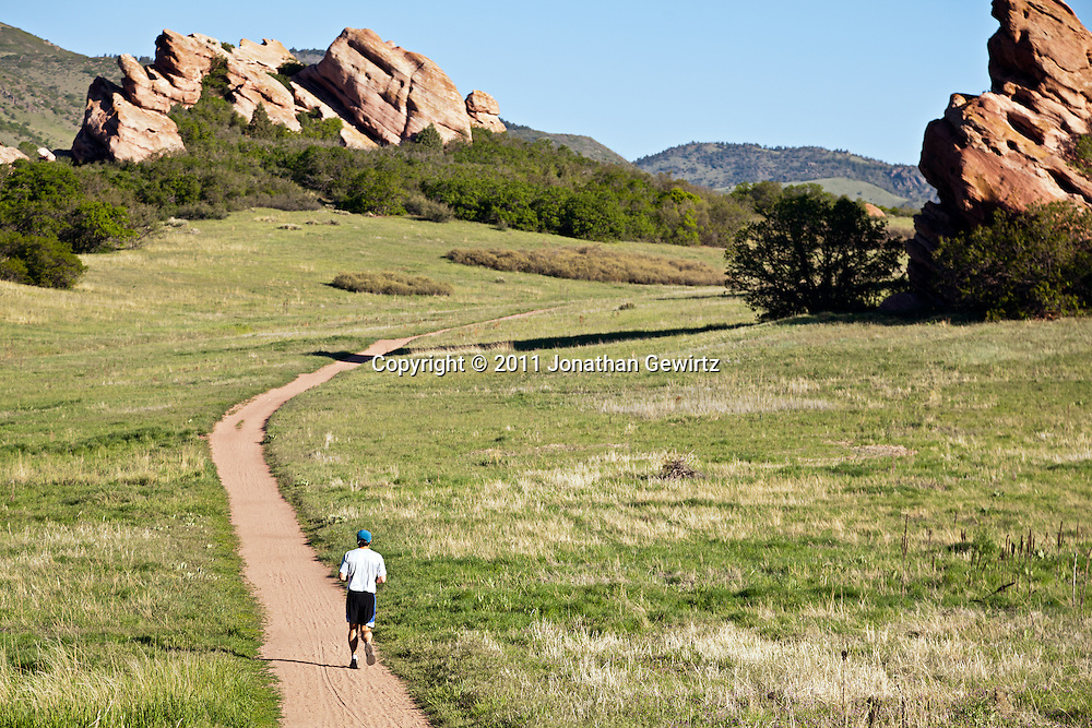 A runner on a path winding through red rock outcroppings in the South Valley Park Ken-Caryl Ranch Open Space in Colorado. WATERMARKS WILL NOT APPEAR ON PRINTS OR LICENSED IMAGES.