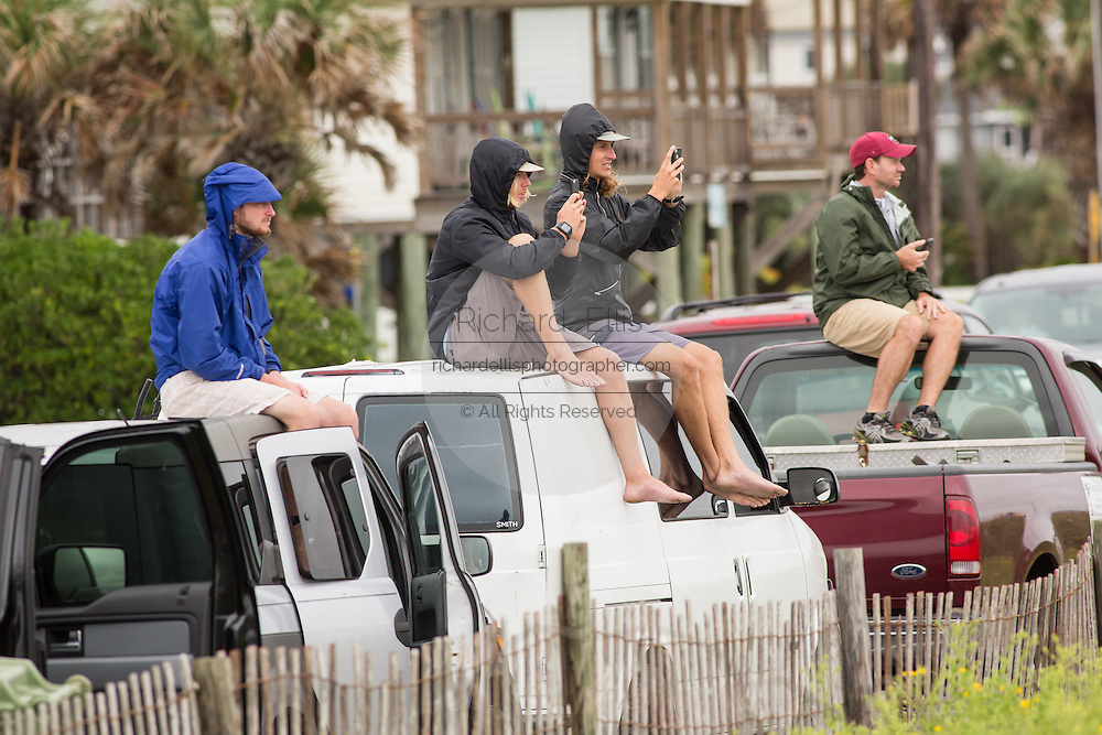 Spectators watch surfers ride big waves at the Folly Washout as Hurricane Joaquin passes off shore bringing high surf and rip tides to the beaches along the South Carolina coast October 2, 2015 in Folly Beach, SC. Joaquin is expected to avoid the Carolinas but has already caused high surf and flooding.