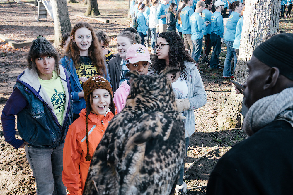 A crowd of volunteers gather to see Hoots, a Eurasian eagle owl, one of several raptors Rodney Stotts cares for at Wings over America.
