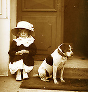 French girl sits in a doorway with a dog. Circa 1900