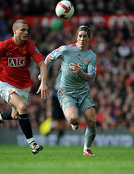 Fernando Torres of Liverpool  challenges Nemanja Vidic of Manchester United during the Barclays Premier League match between Manchester United and Liverpool at Old Trafford on March 14, 2009 in Manchester, England.