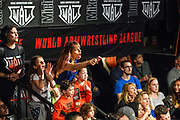 Baltimore, Maryland - May 17, 2018: Deborah Selearis, in the blue, and her nine-year-old daughter Elliana, left, cheer on Mike Selearis, their husband/father respectively during his match against and loss to Frode Haugland during the World Armwrestling League Supermatch Showdown Series at Rams Head Live in Baltimore, Thursday May 17th, 2018. Bleacher Report Live is the exclusive broadcaster of the event. With the recent advent of online video streaming services, niche sporting leagues are now able to sign broadcast deals. <br /> <br /> <br /> CREDIT: Matt Roth for The New York Times<br /> Assignment ID: 30219819A