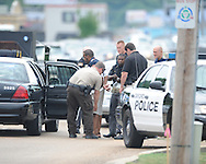 Law enforcement personnel search a suspect following a robbery of the Mississippi Federal Credit Union on West Jackson Avenue in Oxford, Miss. on Wednesday, June 30, 2010.