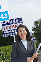 Real estate agent near for sale signs portrait