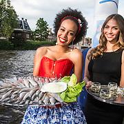 NLD/Amsterdam/20140612 - Hilton Haringparty 2014, twee modellen met Hollandse nieuwe haring en schaal korenwijn