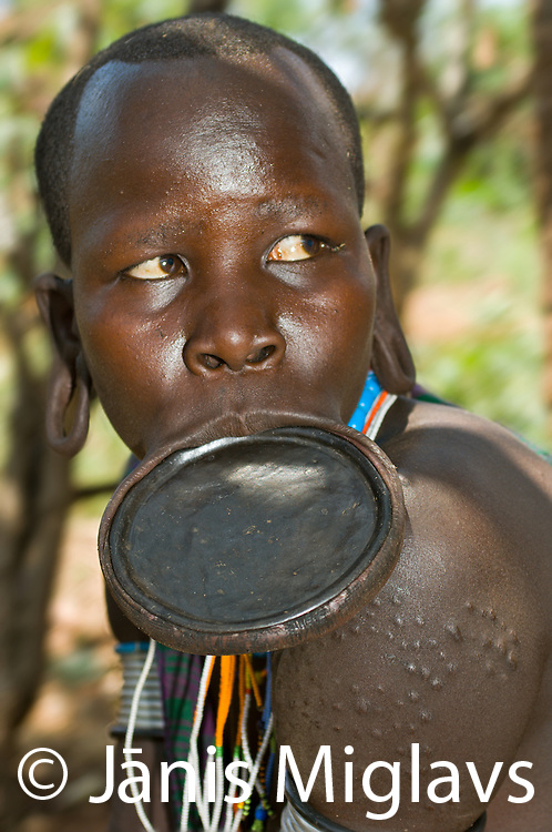 Close up of Suri woman with lip plate and scarification on shoulder working with grinding stone in Regia region, Bargoba village, Omo, Ethiopia.