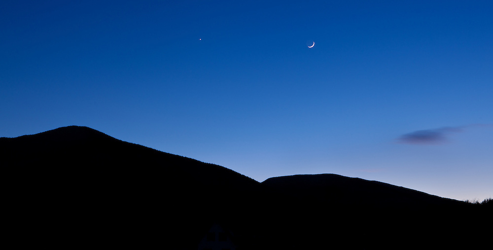Crescent moon setting over a mountain with twilith blue sky, Vermont