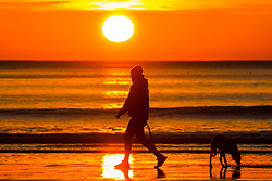 © Licensed to London News Pictures. 02/04/2020. Scarborough UK. A man walks his dog along Scarborough beach as the sun rises this morning on the Yorkshire coast. Photo credit: Andrew McCaren/LNP