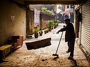 17 MARCH 2017 - KATHMANDU, NEPAL: A worker cleans a sidewalk in an alley at Boudhanath Stupa in Kathmandu. The stupa is the holiest site in Nepali Buddhism. It is also the center of the Tibetan exile community in Kathmandu. The Stupa was badly damaged in the 2015 earthquake but was one of the first buildings renovated.     PHOTO BY JACK KURTZ