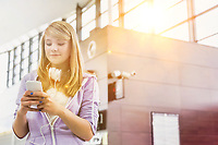 Portrait of young beautiful teenage girl using smartphone in airport with lens flare