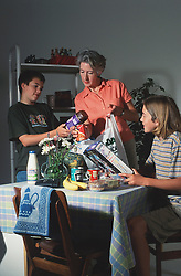 Children helping mother to unpack shopping; mother putting money into wallet,