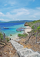 Steps leading down to a beautiful beach with boats moored at a jetty on Pemateran Island, Bali, Indonesia.
