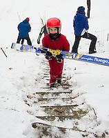 Michael Benenati U10 from Andover Outing Club carries his skis to  the top of the K20 for his practice jump during Gunstock Nordic Associations ski jump meet on Saturday morning.  (Karen Bobotas/for the Laconia Daily Sun)