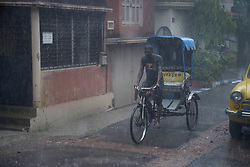 July 23, 2017 - Kolkata, West Bengal, India - Cycle rickshaw puller drenched with rain pull the rickshaw in Kolkata.Overnight rain disrupted city life on July 23, 2017 in Kolkata. Met. Department inform that rain are likely to continue over Kolkata and Gangetic West Bengal during the next 48hrs. (Credit Image: © Saikat Paul/Pacific Press via ZUMA Wire)