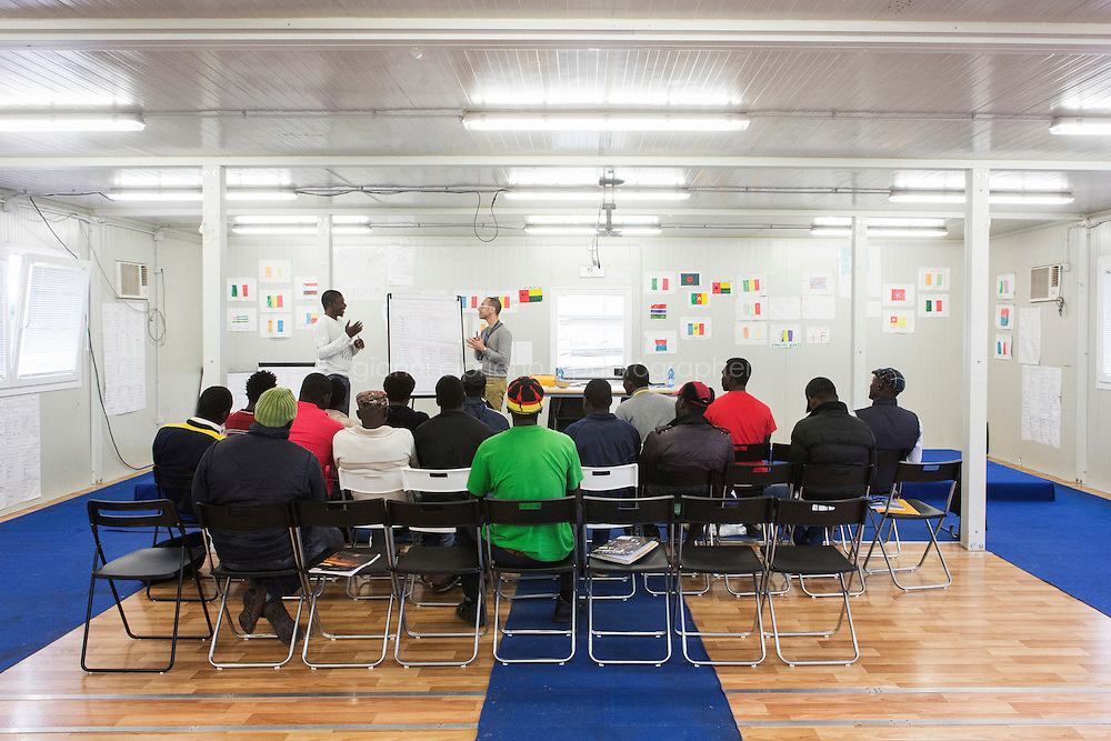 MINEO, ITALY - 26 NOVEMBER 2014: Asylum seekers attend an Italian language class at the CARA (Accommodation Centre for Asylum Seekers) in Mineo where approximately 4,000 asylum seekers live, in Mineo, Italy, on November 26th 2014.<br /> <br /> By law, asylum-seekers can be held for 35 days in a CARA. In reality, the average stay is closer to a year.The Cara is located at the &quot;Residence degli Aranci&quot; (Residence of the Oranges), a small town built to accomodate the families of US soldiers operating at the Naval Air Station of Sigonella 40km away. Since 2011 the &quot;Residence degli Aranci&quot; hosts the Accommodation Center for Asylum Seekers, which has since then hosted more than 12,000 seekers of 47 nationalities and over 200 ethnic groups. The CARA of Mineo includes 404 houses. Each house hosts from 7 to 11 asylum seekers.
