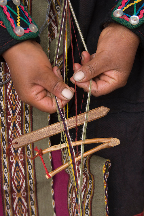 South America, Peru, Chinchero (near Cuzco), hands weaving belt using backstrap loom.