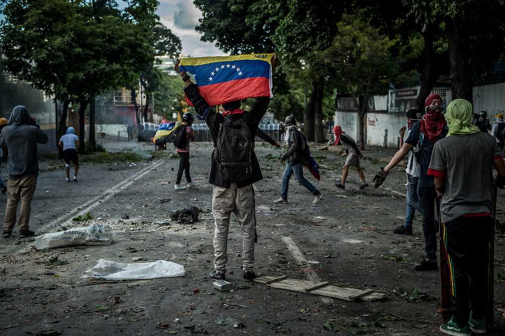 CARACAS, VENEZUELA - JULY 26, 2017: A member of La Resistencia holds up the flag of Venezuela during clashes with soldiers during an anti-government protest to demand that the National Constituent Assembly election scheduled for Sunday, July 30th be cancelled. The political opposition called for a 48 hour national strike on July 26th and 27th, and for their supporters to close businesses, not go to work, and instead create barricades to block off their streets.  Opposition controlled areas of the country were completely shut down.  The strike was called as part of the opposition's civil resistance movement - that began on April 1st, to protest against the Socialist government's attempt to elect a new assembly that will have the power to re-write the constitution, and their opposition to the Socialist's continued threats to Venezuelan Democracy.  PHOTO: Meridith Kohut for The New York Times