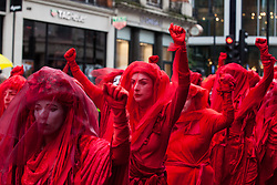 London, UK. 12 October, 2019. The Red Brigade lead thousands of fellow climate activists from Extinction Rebellion on the XR funeral march from Marble Arch to Russell Square on the sixth day of International Rebellion protests to demand a government declaration of a climate and ecological emergency, a commitment to halting biodiversity loss and net zero carbon emissions by 2025 and for the government to create and be led by the decisions of a Citizens' Assembly on climate and ecological justice. Credit: Mark Kerrison/Alamy Live News
