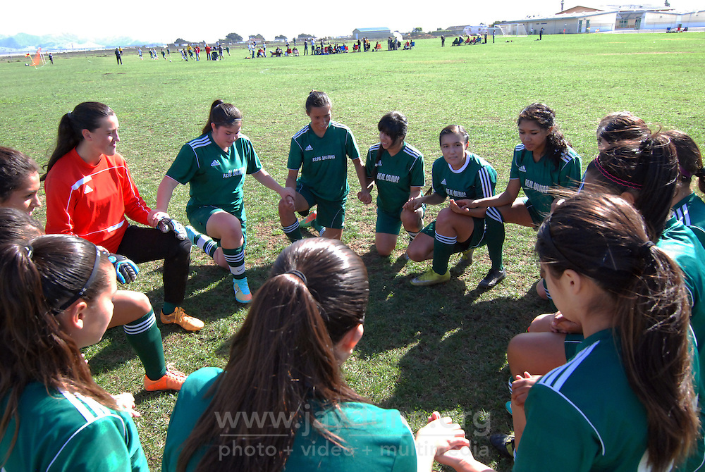 "The U-17 Real Salinas Thundergirls say a prayer together before their final tournament game of 2014 versus San Bruno at Bolsa Knolls Middle School in Salinas. The El Camino Real Futbol League is a 501(c)3 non-profit corporation, whose stated mission is ""to provide the youth of Monterey County with the attributes to achieve success in their lives through academic excellence and knowledge of a healthy lifestyle through the game of soccer."""