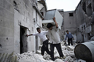 SYRIA, ALEPPO. A Syrian man carries away a fridge from the remains of destroyed houses following an airstrike by the Syrian airforce in the northern Syrian city of Aleppo. ALESSIO ROMENZI