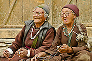 Two very old women with wrinkled face prayeng with beads in Ladakh, India