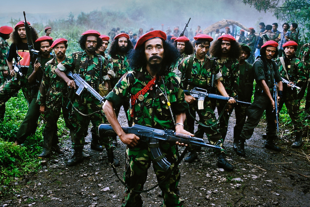 Falintil Commander Cornelio Gama, with some of his guerrilla force. <br /> <br /> Falintil meaning: 'National Armed Forces for the  Liberation of East Timor'. <br /> <br /> The red berets are worn on special occasions and only by soldiers who are veterans of the conflict.<br /> <br /> East Timor, March 1999.