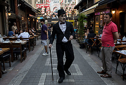 July 3, 2018 - Kadikoy, Istanbul, Turkey - A retired officer, Mustafa Guneyli, wears the costume of 'Charlie Chaplin', puts on his make up every single day goes out on the streets of Kadikoy, Istabul District, Turkey, on 7 July 2018. He thinks that people always look so unhappy or sad on the streets but everyone smiles, gets surprised, hugs or tries to take photos with him when they see the local Chaplin around. He is now the ''Charlie Musti Chaplin'' of Kadikoy. (Credit Image: © Erhan Demirtas/NurPhoto via ZUMA Press)