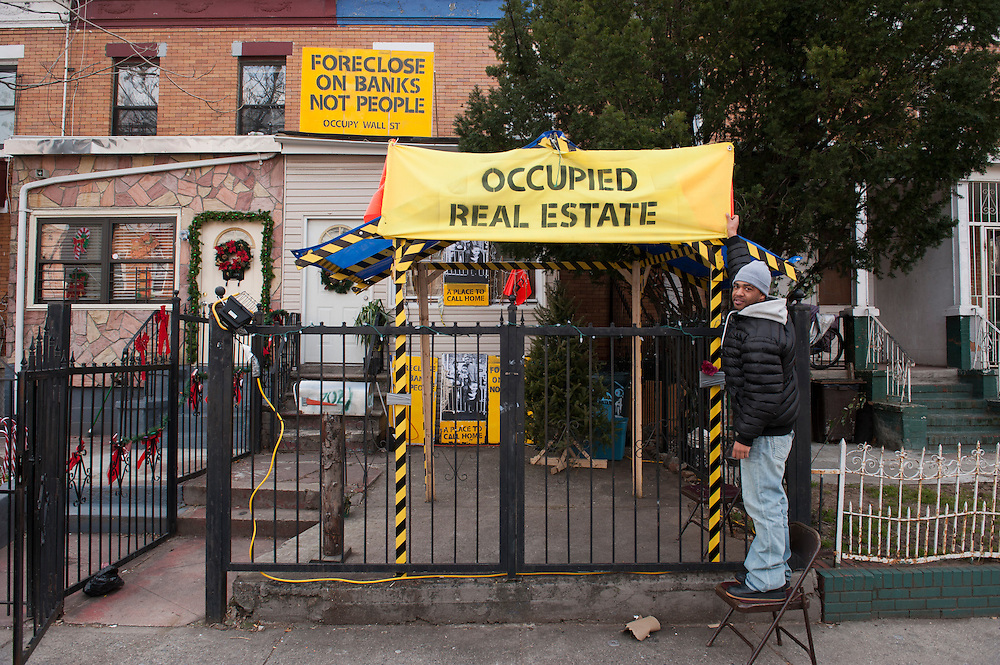 Occupy Housing.Homeless activist Alfredo Carrasquillo, 28, in front of the occupied house in East New York, Brooklyn, with a photo of his wife and two children..The East New York foreclosed home had been vacant for three years before for Alfredo Carrasquillo and others took it over for Occupy Wall Street....photo © Stefan Falke.
