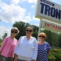 From left, LuEllen Children, Amy Webb and Gayle Jarrell stand in front of Tronox's entrance sign. The Hamilton industry is the first corporate sponsor for the potential Monroe County Children's Vision Center.